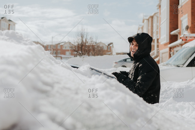 Man laughing beside snow-covered vehicle, Toronto, Canada