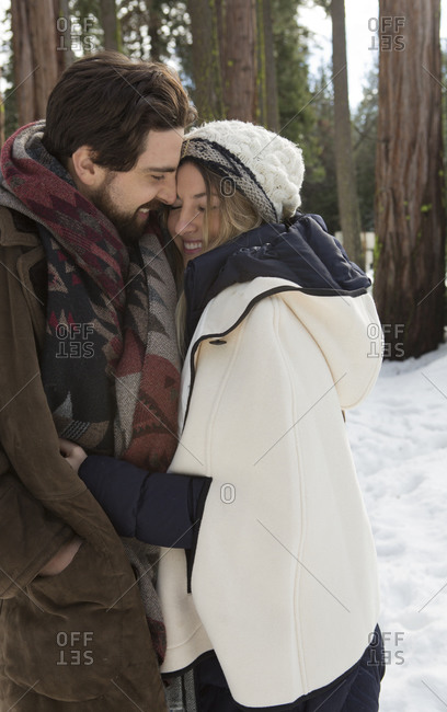 Young woman and boyfriend hugging in winter forest, Twain Harte, California, USA