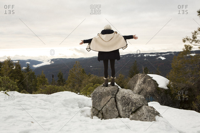Young woman standing on rock on snow covered mountain, rear view, Twain Harte, California, USA