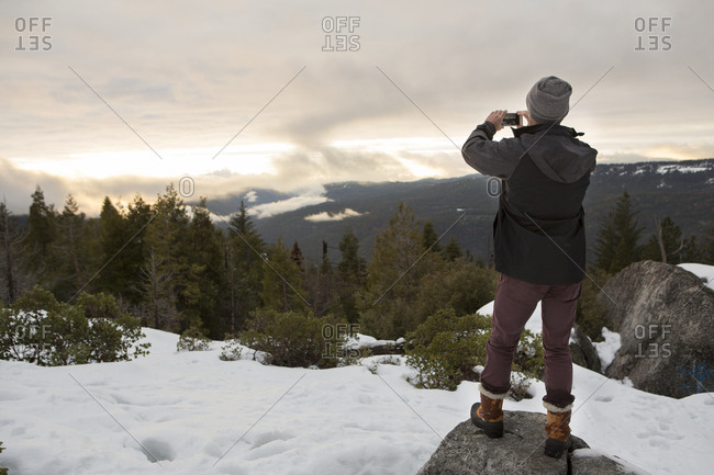 Mid adult man photographing view from rock on snow covered mountain, rear view, Twain Harte, California, USA