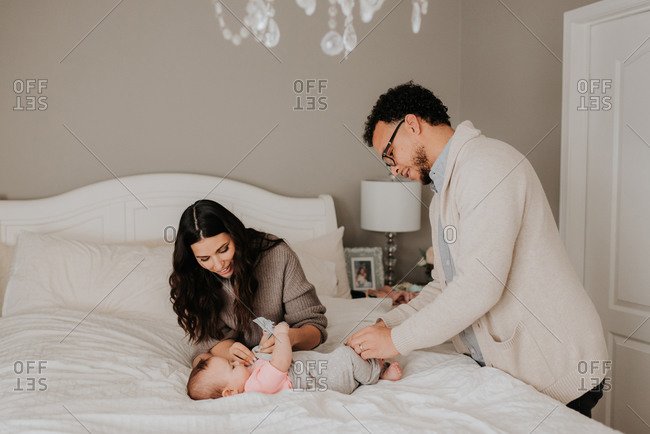 Couple dressing baby daughter on bed in bedroom