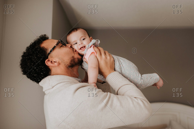 Father kissing baby daughter lovingly