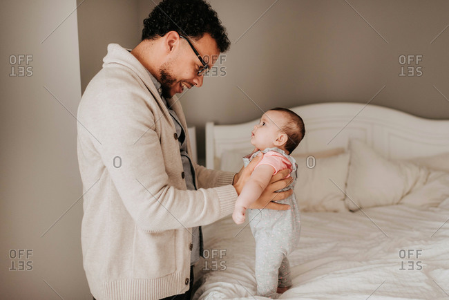 Father talking face to face with baby daughter