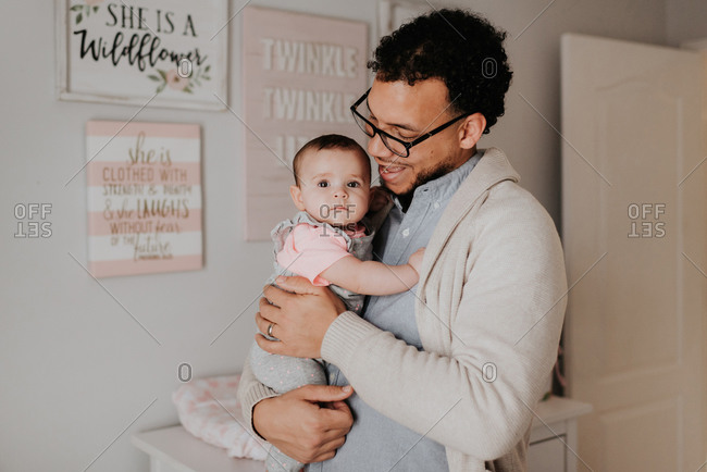 Father with baby daughter in baby's room