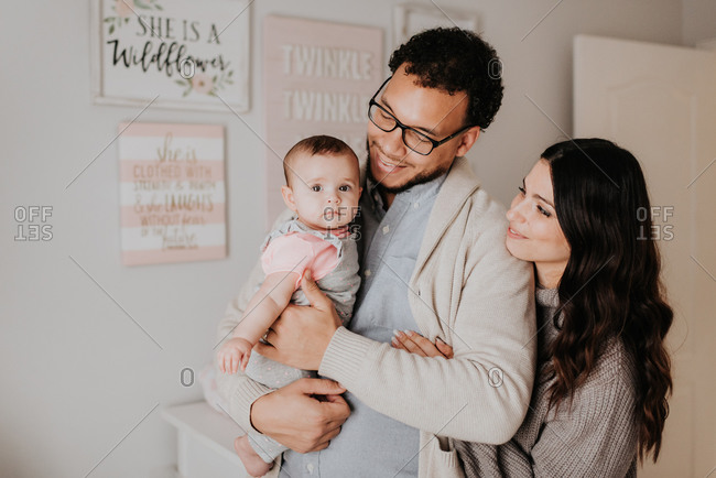 Couple with baby daughter in baby's room