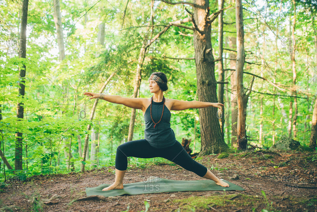 Woman doing warrior pose in forest