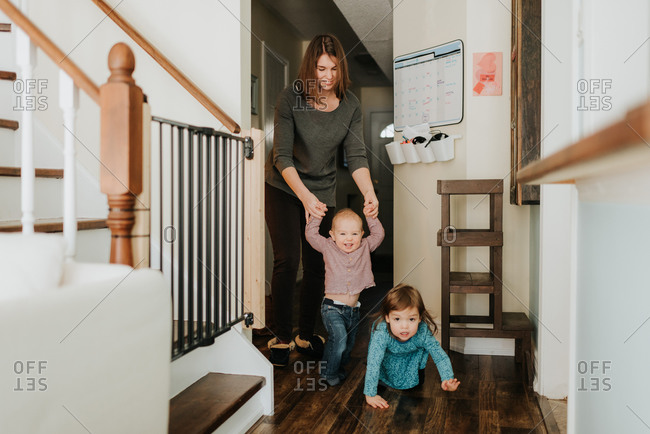 Mother with toddler daughter walking baby son in hallway
