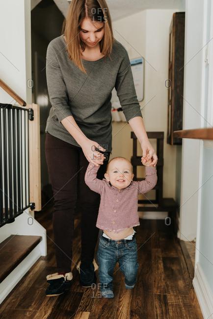 Mother walking baby son in hallway