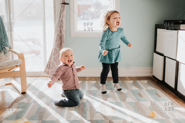 Female toddler and baby brother playing on living room rug