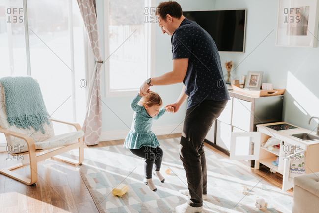 Father playing with toddler daughter on living room rug