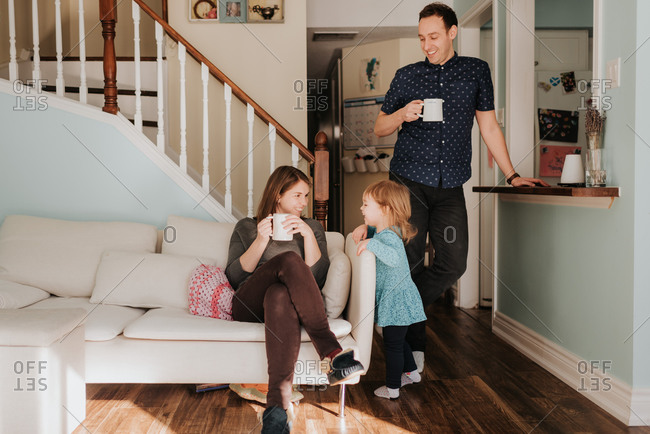 Mid adult couple having mug of coffee in living room with toddler daughter