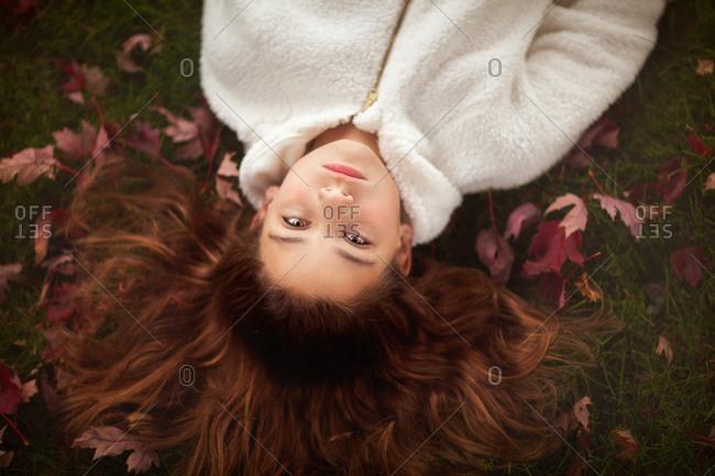 Girl with long auburn hair lying on grass amongst autumn leaves, portrait