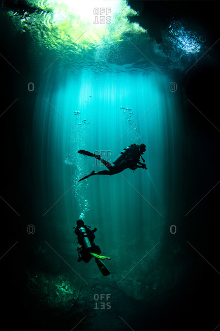 Underwater view of male and female scuba divers exploring cenote called the pit, Tulum, Quintana Roo, Mexico