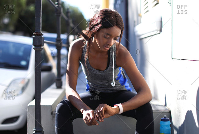 Young female runner sitting on city sidewalk looking at smartwatch