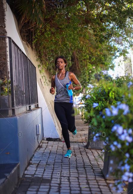 Young female runner listening to earphones running up city sidewalk