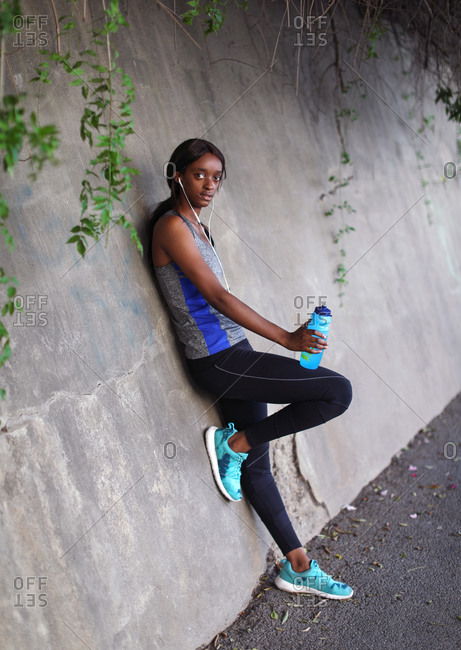 Young female runner listening to earphones leaning against wall on city sidewalk, portrait