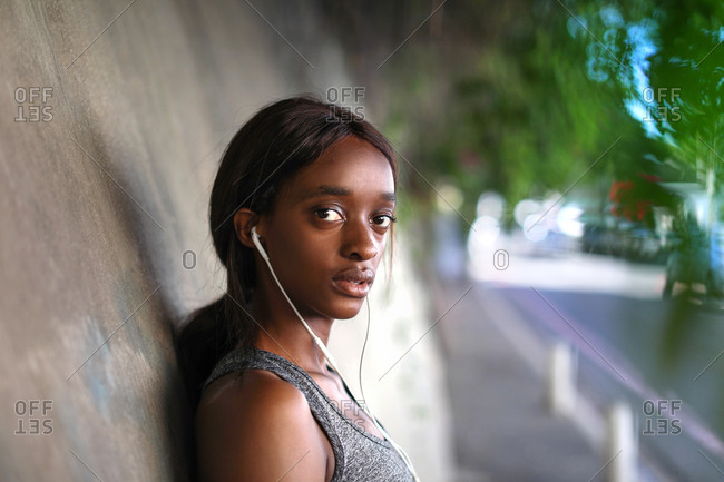 Young female runner listening to earphones on city sidewalk, head and shoulder portrait