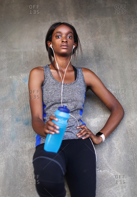 Young female runner listening to earphones leaning against  wall, portrait