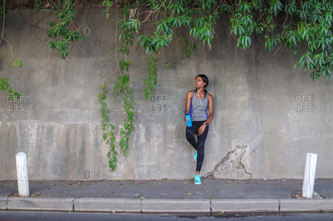Young female runner listening to earphones leaning against  city sidewalk wall
