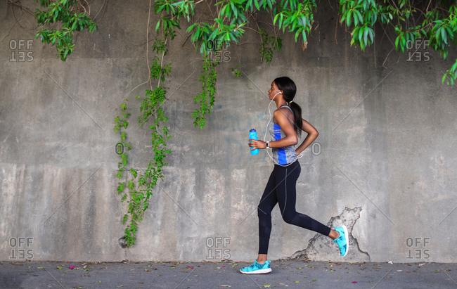 Young female runner running along city sidewalk