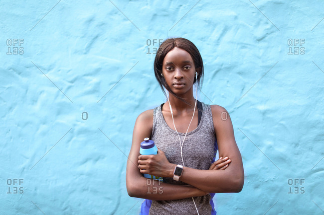 Young female runner in front of turquoise wall, waist up portrait