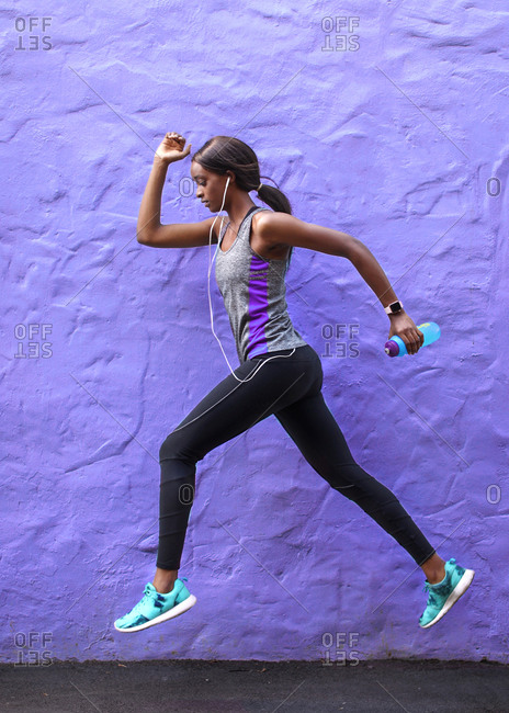 Young female runner running in front of purple wall, full length
