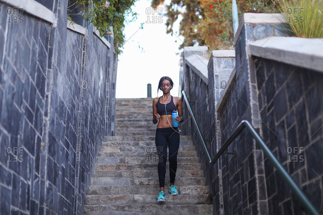 Young female runner running down city stairway