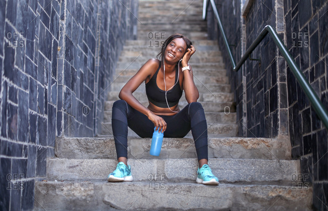 Young female runner listening to earphones taking a break on city stairway, portrait