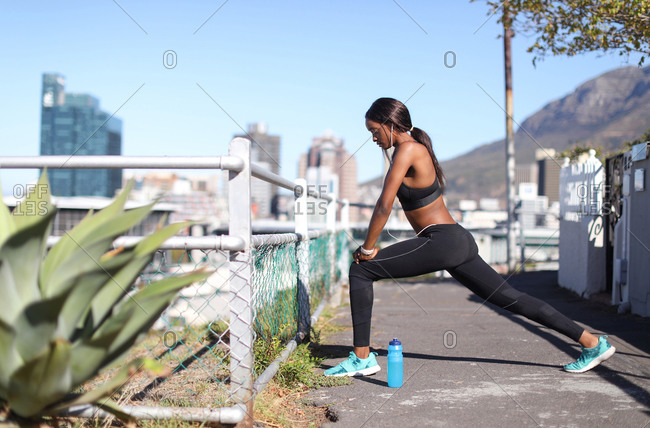 Young female runner listening to earphones stretching on city stairway, Cape Town, Western Cape, South Africa