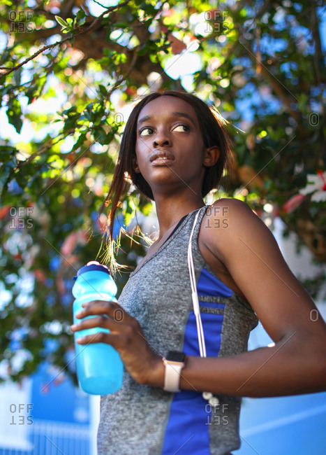 Young female runner holding water bottle under tree, looking sideways