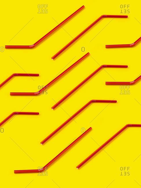 Red straws laid diagonally on yellow background