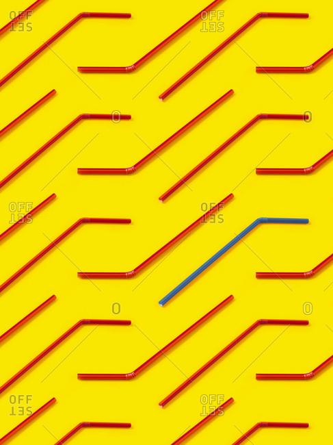 Red and blue straws laid diagonally on yellow background