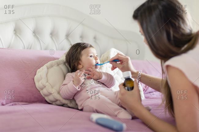 Mother feeding baby girl medicine in bed