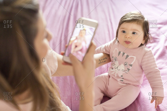 Mother taking photograph of baby girl on bed