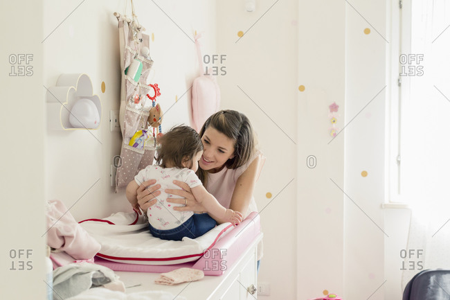 Mother talking to baby girl on changing table