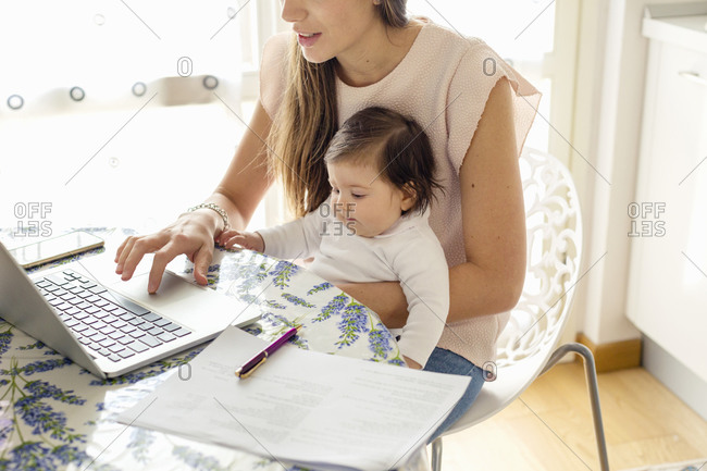 Mother working on laptop with baby girl on lap at home