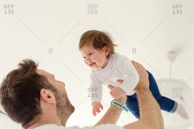 Father playing with baby girl at home