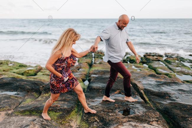 Couple walking on rocks, Estoril, Lisboa, Portugal