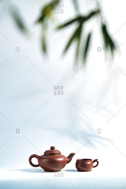 Tea pots with bamboo leaves in the background
