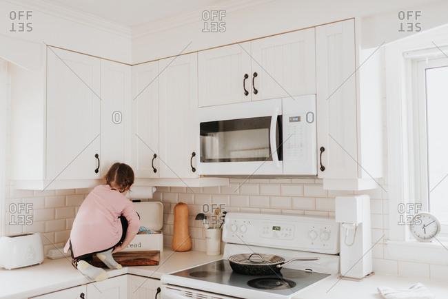 Girl tidying bread bin on kitchen worktop