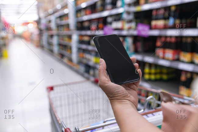 Middle-aged women holding a mobile phone in supermarket