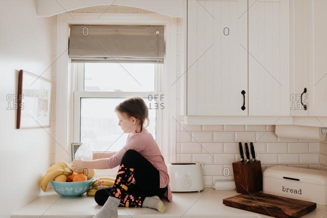 Girl arranging fruits in basket on kitchen worktop