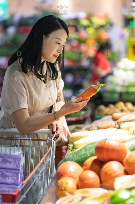 Middle-aged women chooses vegetables in supermarket