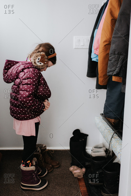 Girl putting on jacket in cloakroom