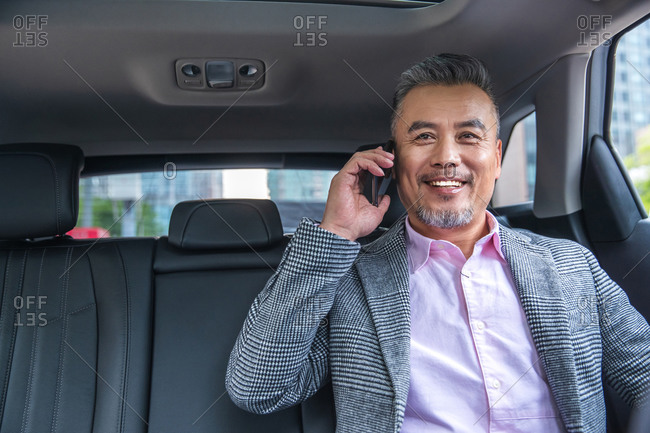 Middle-aged businessman takes a call in his car