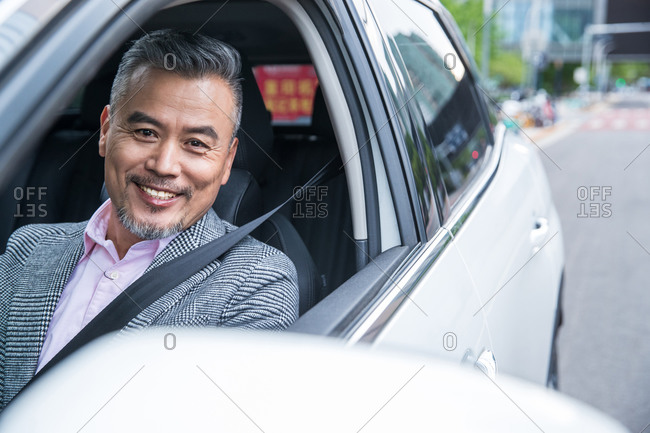 Middle-aged business man driving a car
