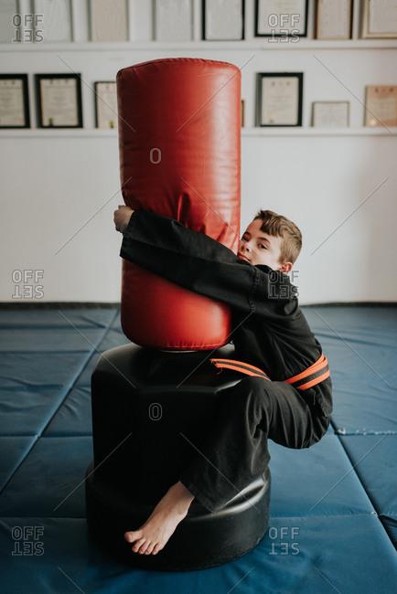 Boy clinging onto punch bag in martial arts studio