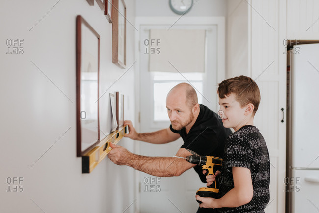 Father teaching son drill wall for picture frames
