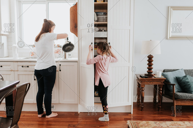 Mother pouring hot water, girl looking into cabinet in kitchen