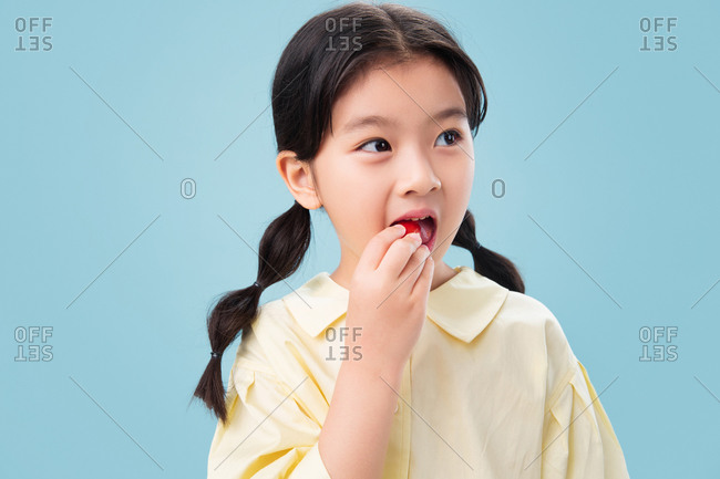 Little girl eating happily eating fruit